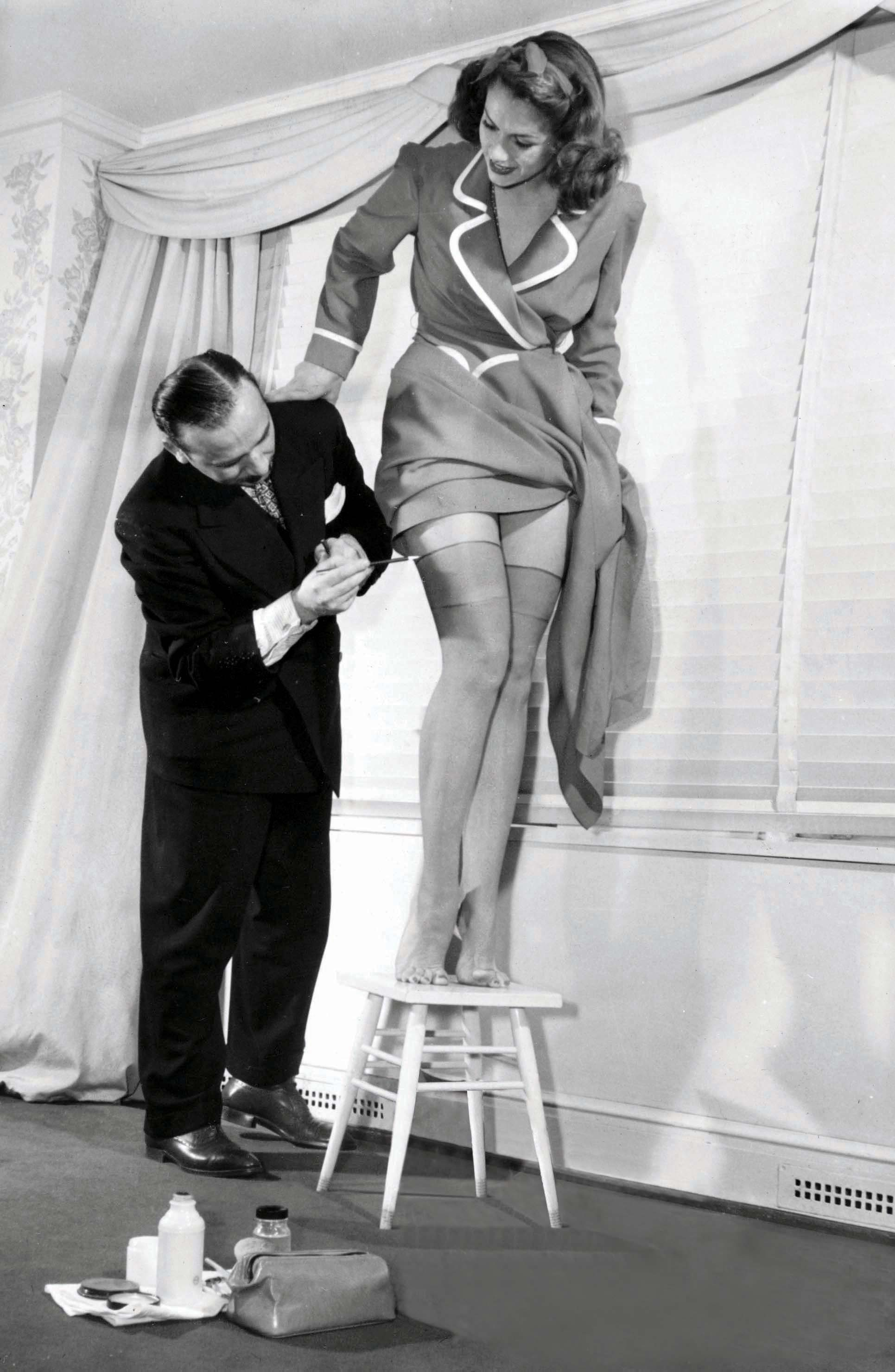 During the Second World War, there was a nylon shortage; here, a woman stands on a stool while a man carefully paints on her stockings