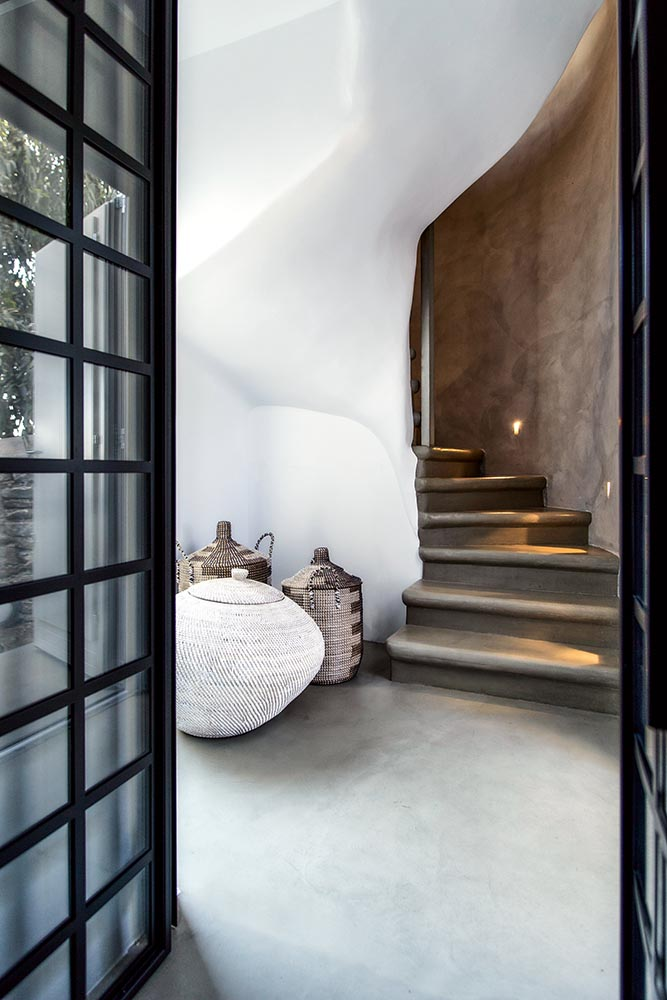 A sinuous, brushed concrete staircase at a house in Chora
