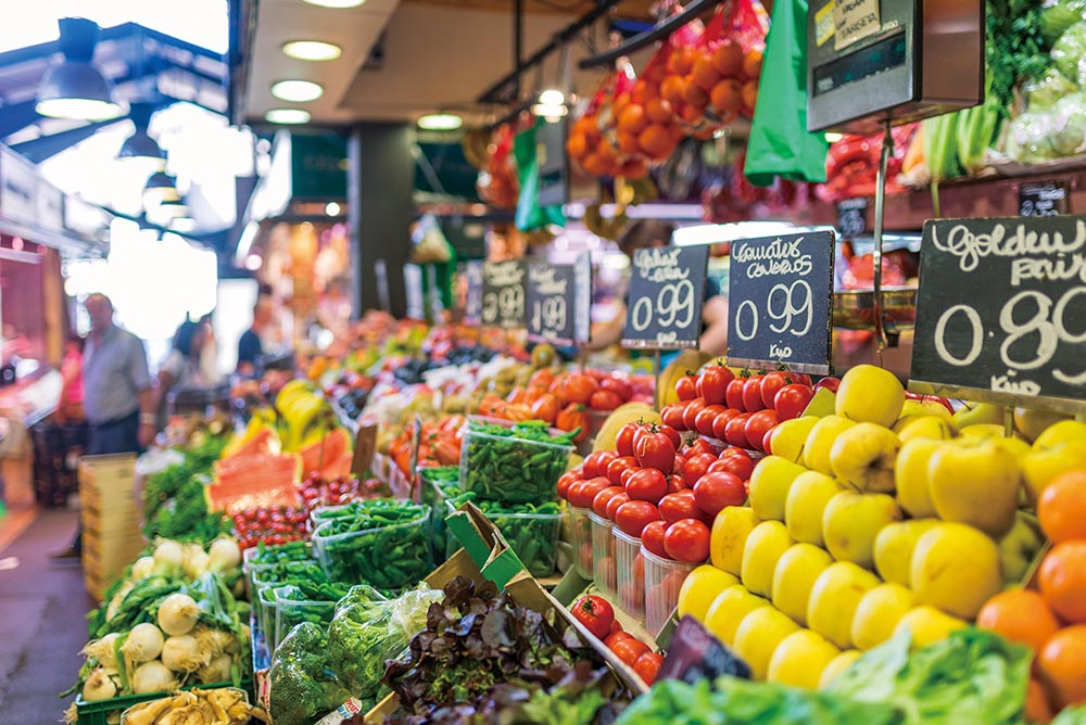 Greengrocer at public market La Boqueria Barcelona