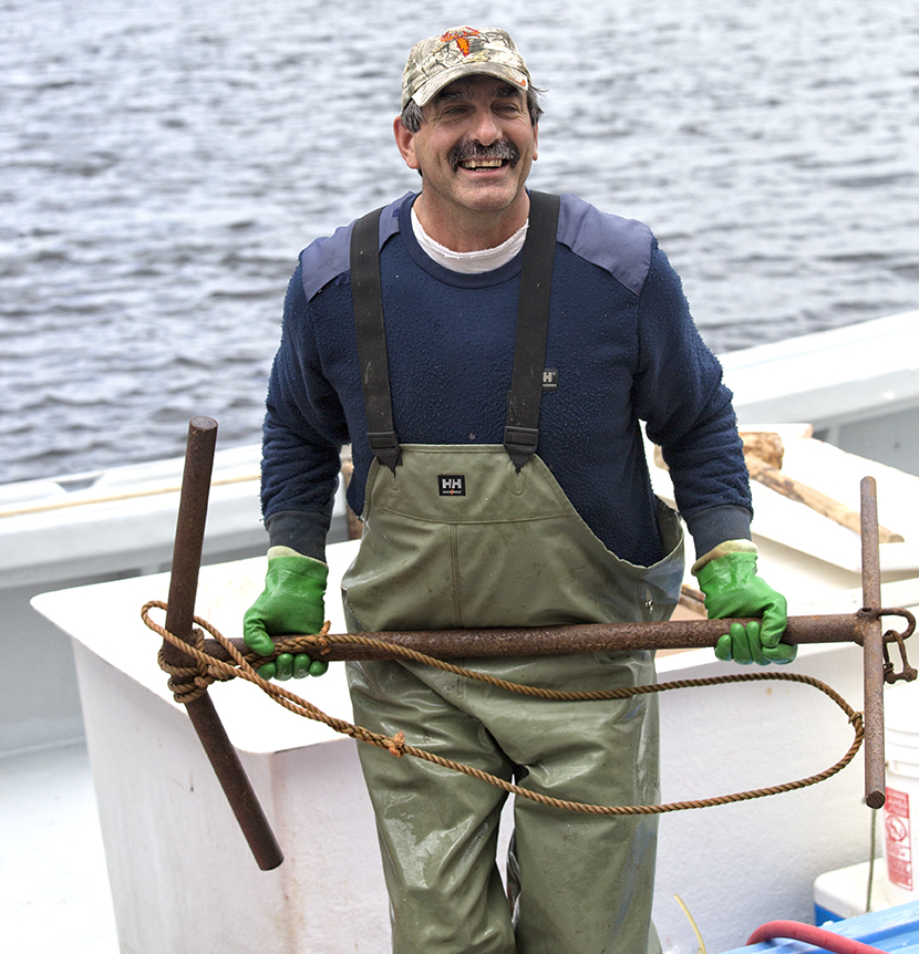 A lobsterman in Gabarus, Cape Breton pulls up the anchor.