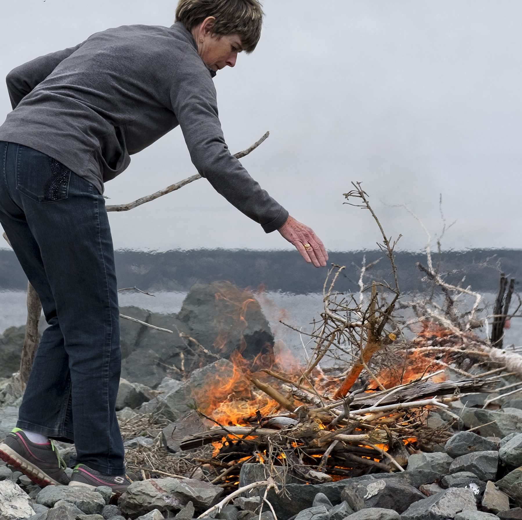 Maureen Kavadias gathers sticks in Gabarus and starts a fire for the lobster boil.