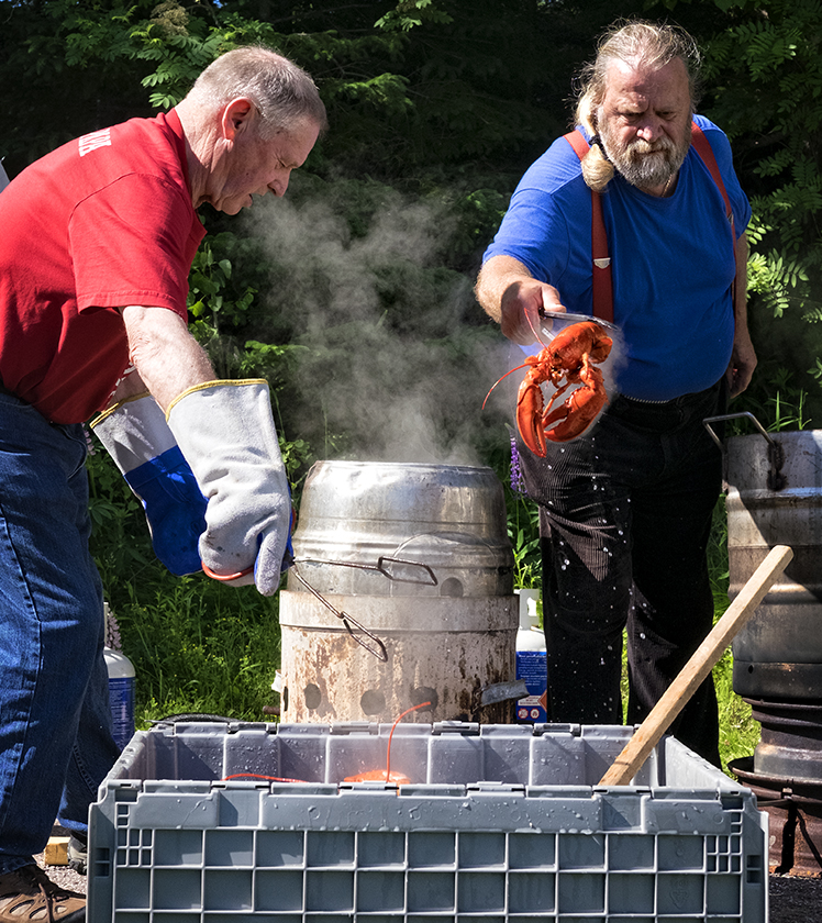 One of the many lobster festivals, this one held at the Mira Center in Marion Bridge, Cape Breton. A man tosses the cooked lobster into a crate of cold water to cool.