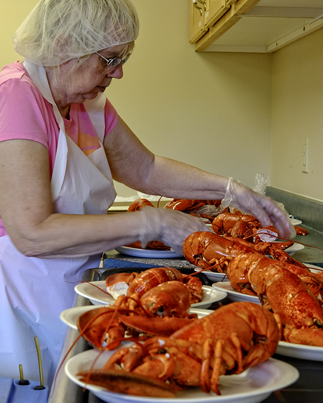 In the kitchen behind the scenes, a volunteer plates the lobsters for waiting guests of the festival. Marion Bridge, Cape Breton.