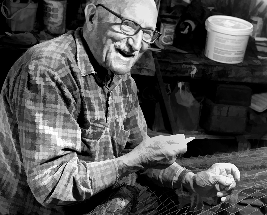 Ron Ingram came from New Foundland to Neil's Harbour when he was 18. He mends fishing nets, a dying art, in the basement of his home...