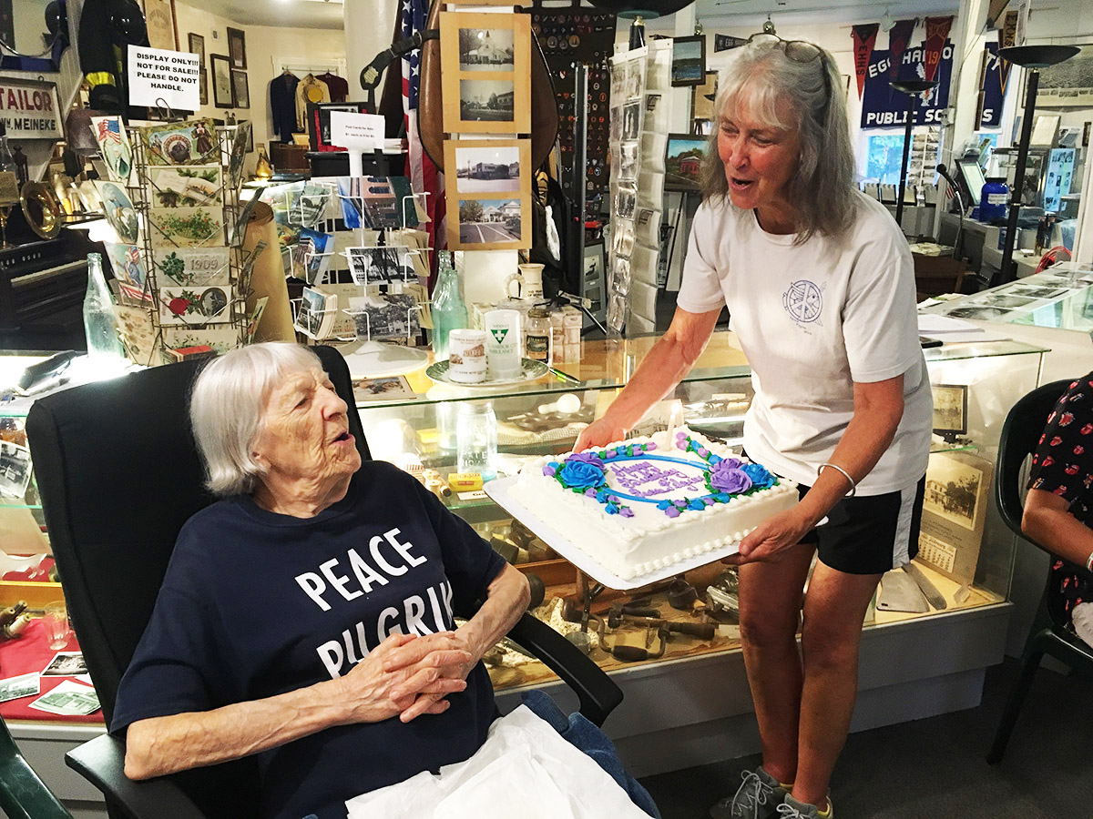 Peace Pilgrim's sister, Helene Young (age 104) gets ready to blow out the candle on the birthday cake held by FoPP board member Barbara Reynolds