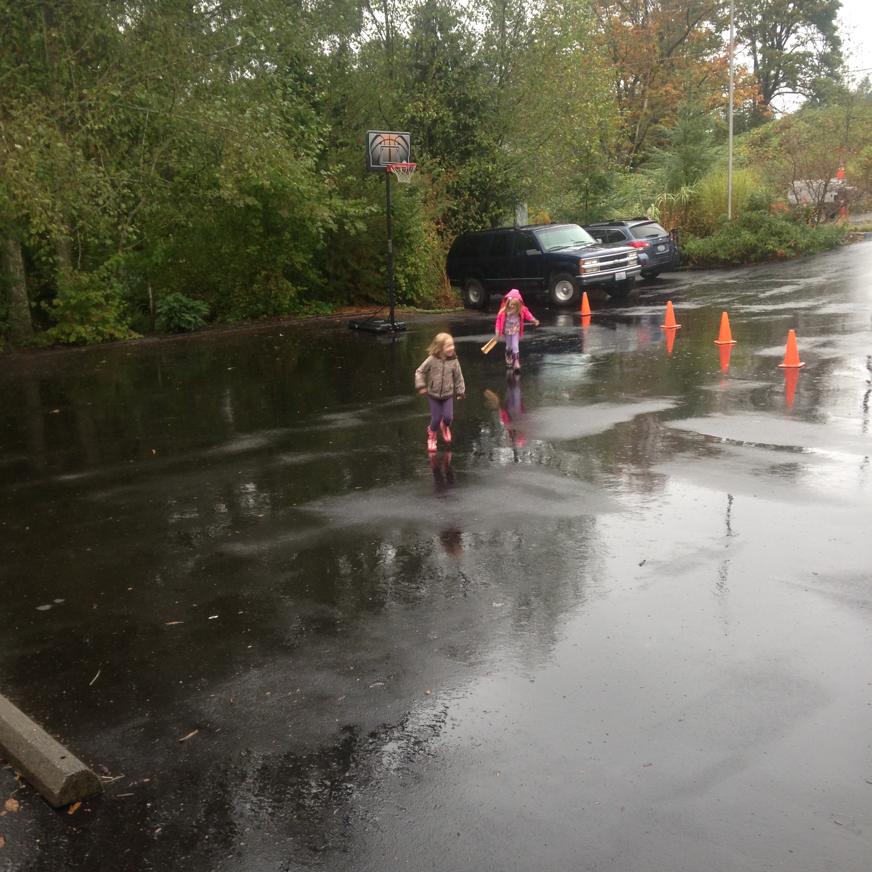 两个年轻的学生在停车场一个被封锁的地方玩水坑.