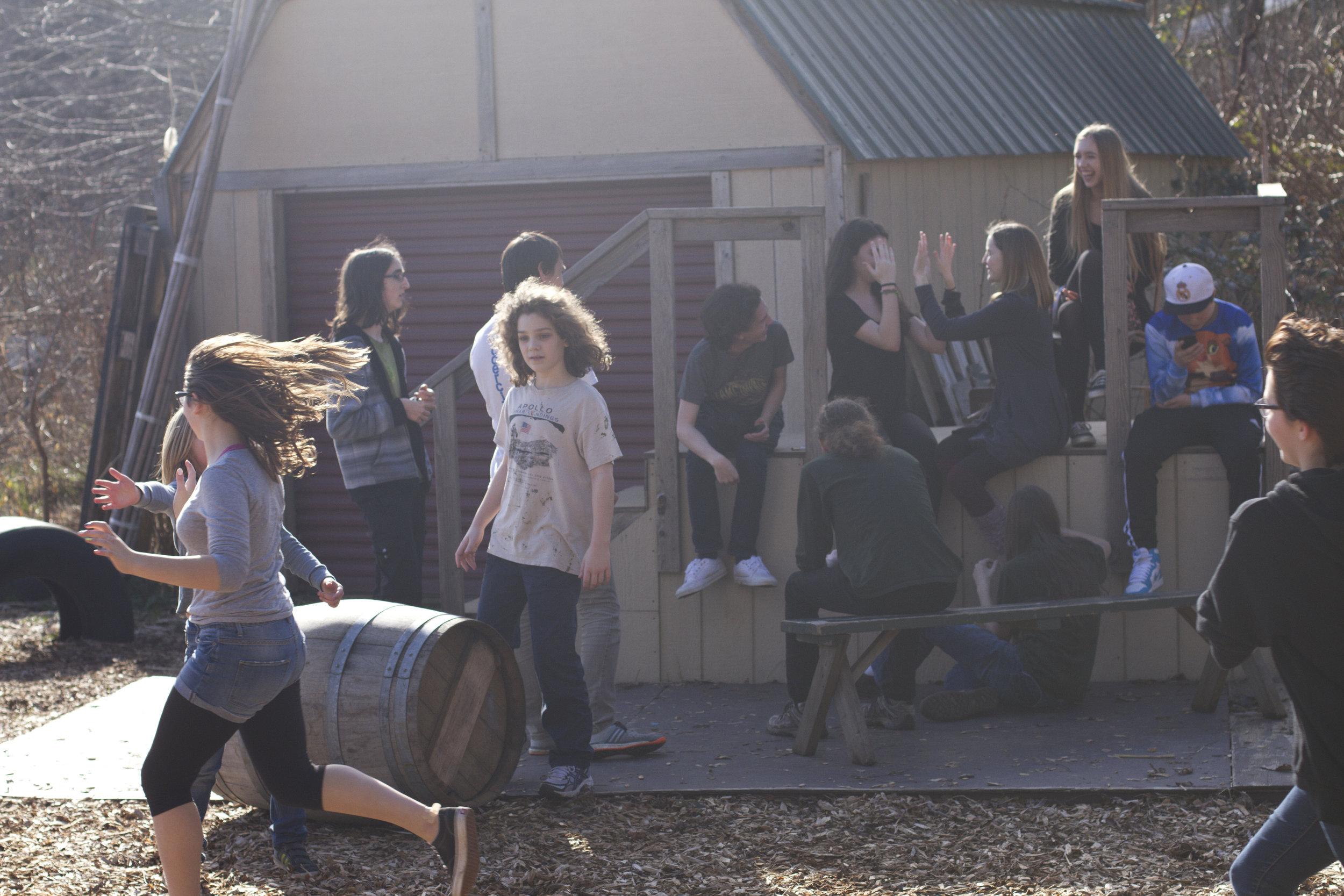 外面有一大群学生, 挤在两个正在玩拍手游戏的学生周围.