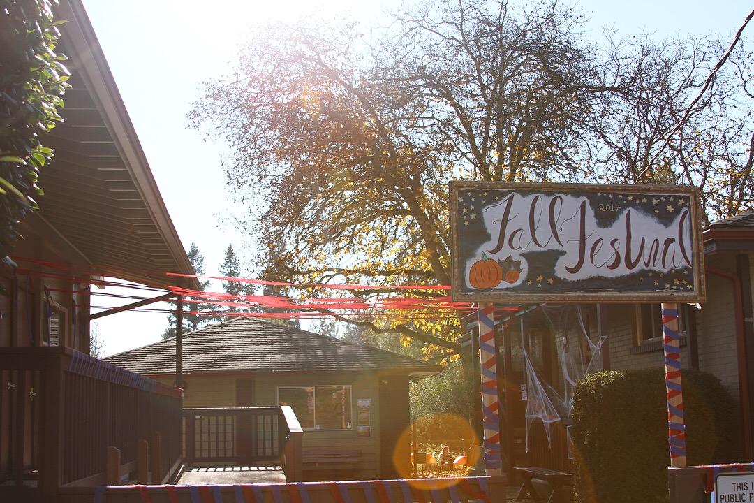 """校园入口. 一个标志上写着""""2017秋季节"""",建筑上有节日装饰."""