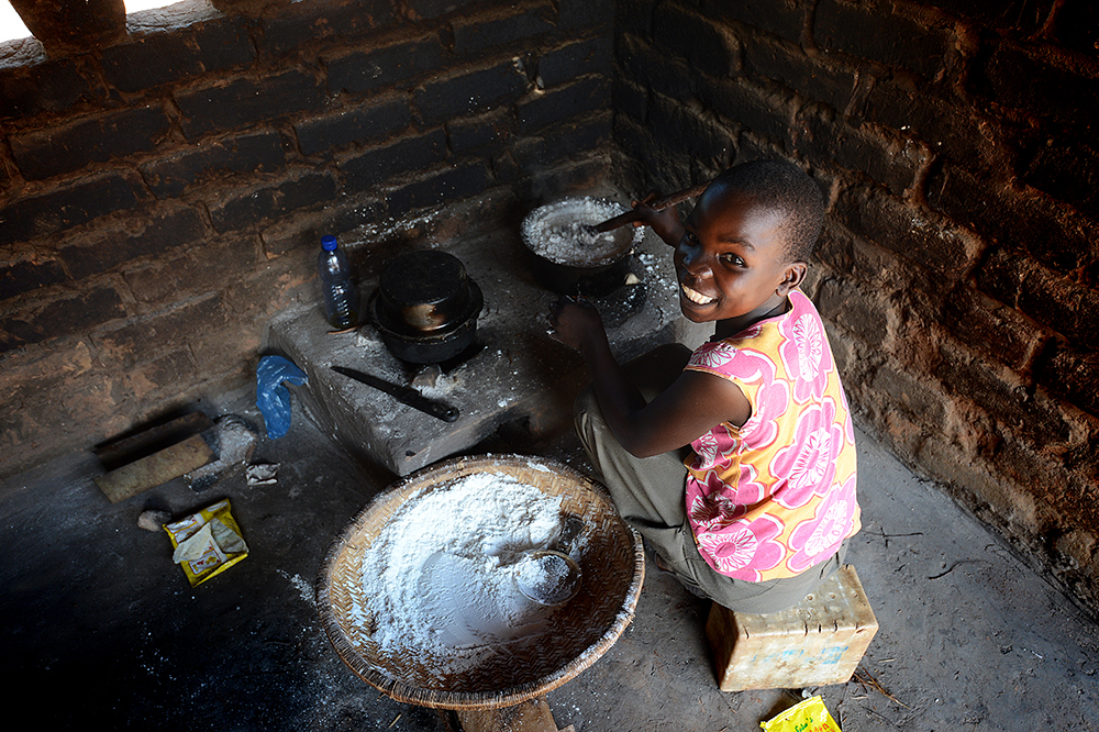 The Mtikas' eldest daughter, Dorothy, making nsima for dinner in the family's new, more environmentally-friendly kitchen.  More people die around the world from smoke inhalation from indoor cooking than from HIV and malaria combined -- the Mtikas' new cookstove burns less fuel and has better ventilation than their old one.