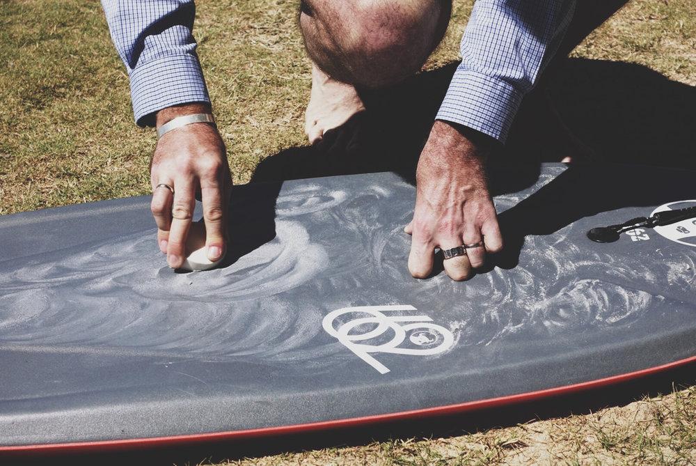 Marcus waxing his board.