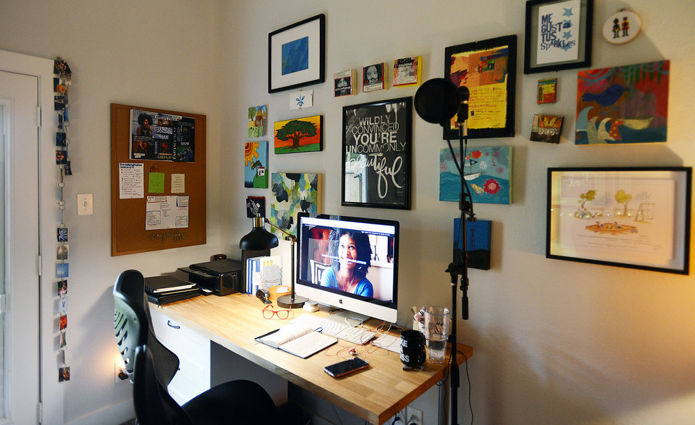 The view in front of me when I sit at my desk in my tiny office. The art is primarily art made by friends and family. I plan to continue adding up to the ceiling and to the floor. Because why not?