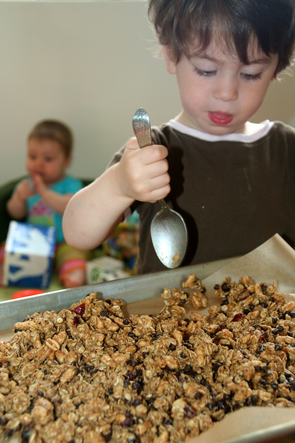 My son spreading granola bars onto a cookie sheet for Food Revolution Day 2013