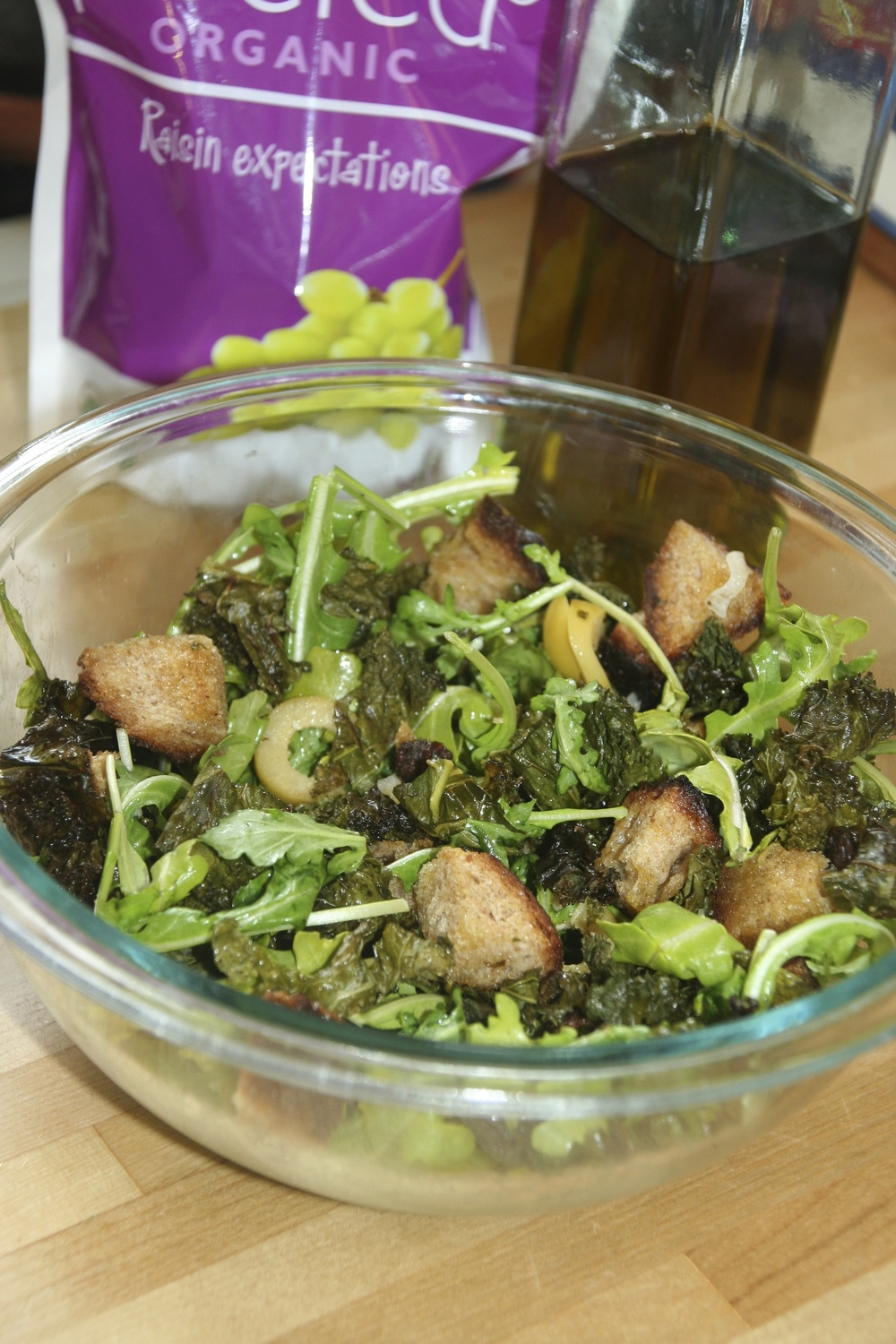 I assembled the salad by tossing the kale with arugula, green olives (that I sliced), 1/4 cup of my favorite raisins from Peeled Snacks and fresh chopped cilantro. I squeezed fresh lemon juice and sprinkled with salt and pepper and tossed in the croutons and roasted shallots at the very end. YUM.