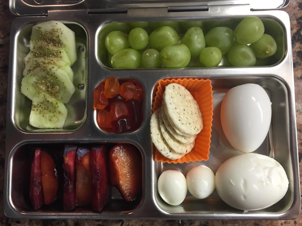 various eggs, crackers,plum, cucumber with herb salt, grapes, Annie's fruit gummies