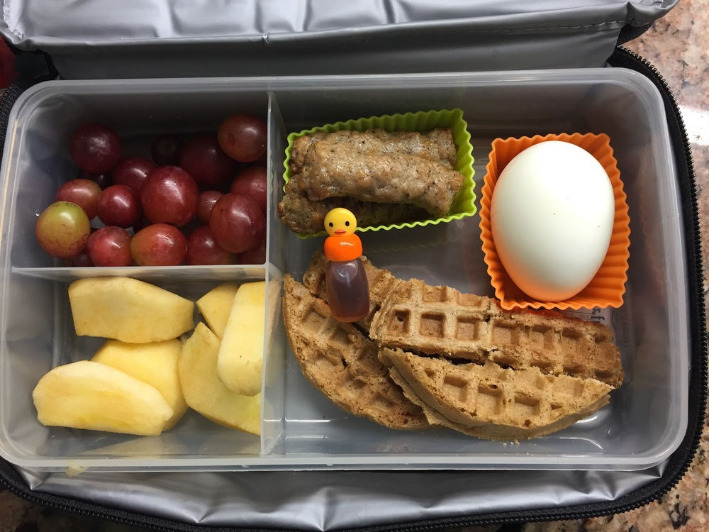 Breakfast for lunch! Waffles, mini maple syrup, egg, chicken apple sausages, apple, grapes.
