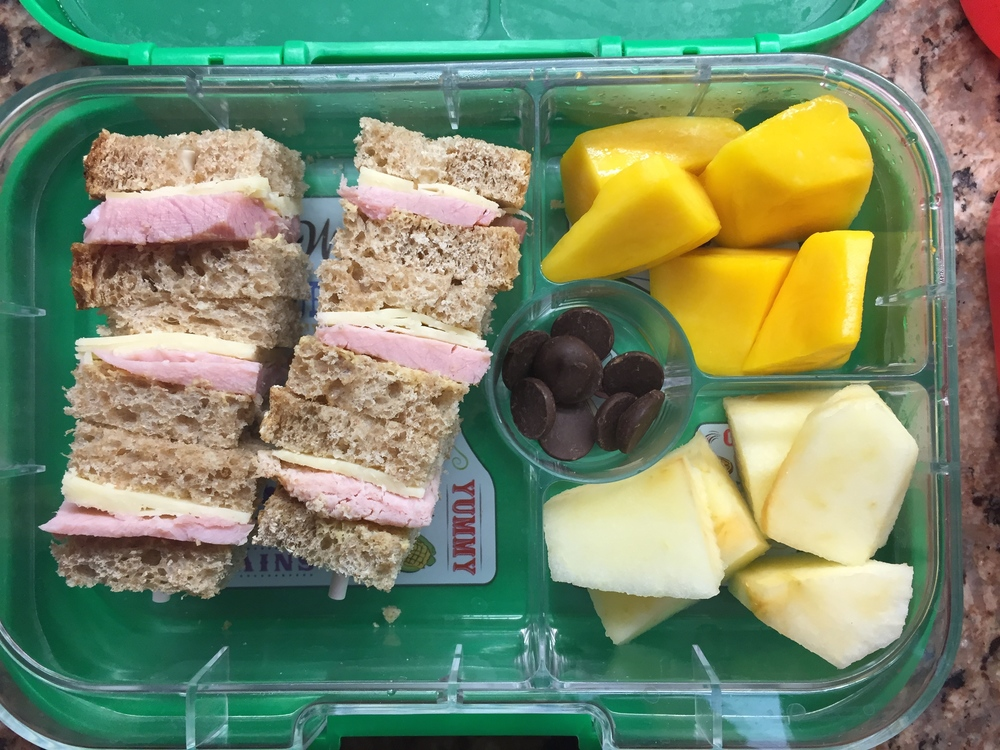 Ham and cheese sandwich kebabs, mango, apple, chocolate chips.