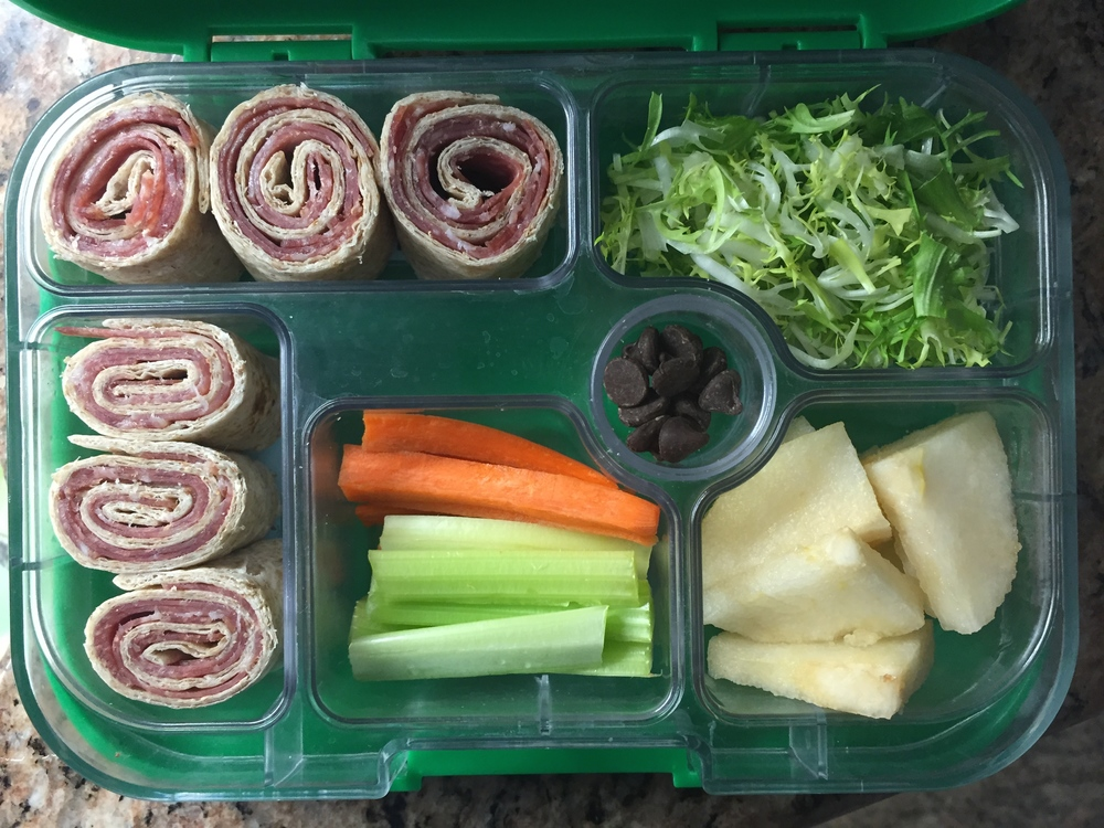 Roll ups with salami, salad, apple, celery and carrots, chocolate chips.