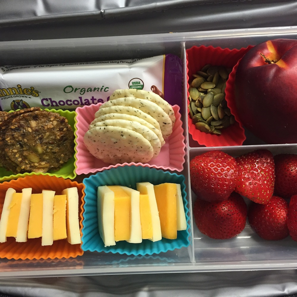 Cheese and crackers, strawberries, nectarine, pumpkin seeds, granola bar.
