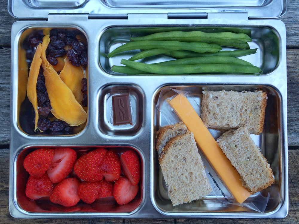 Cheddar cheese stick, whole grain bread with butter, green beans, strawberries, dried mango and raisins, and a small piece of chocolate.