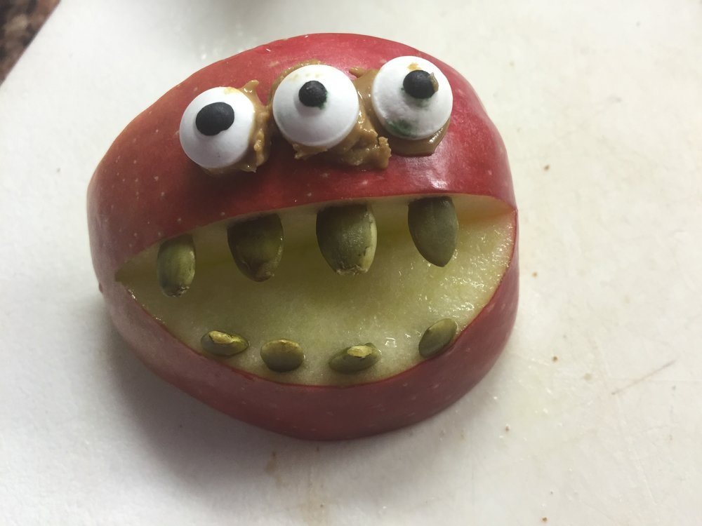 Apple monster with sunflower seed teeth and eyeballs affixed with sunflower seed butter.