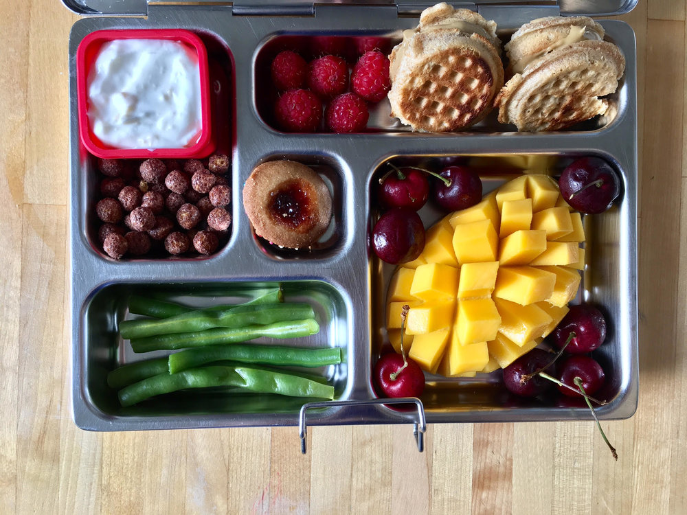 mango and cherries, wafflewiches with sunflower seed butter, raspberries, yogurt and cereal, green beans and a thumbprint cookie
