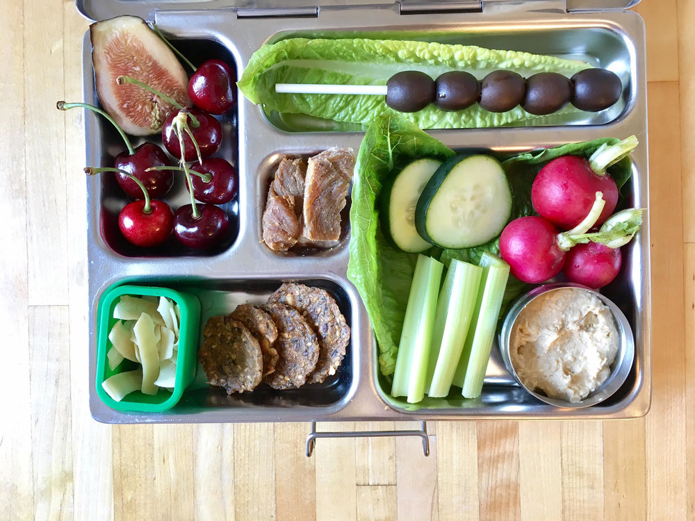 hummus with celery, cukes and radishes, black olives, turkey jerky, crackers, coconut chips, cherries and fig