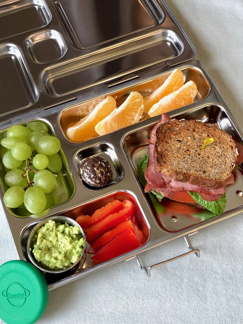 In the lunchbox: Turkey BLT with guacamole and peppers, grapes and orange.