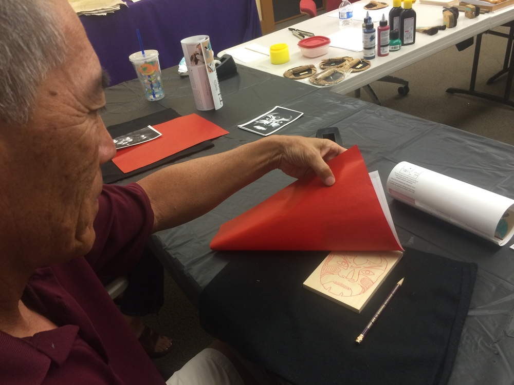 Transferring a photograph of a kabuki mask to a woodblock using carbon paper.