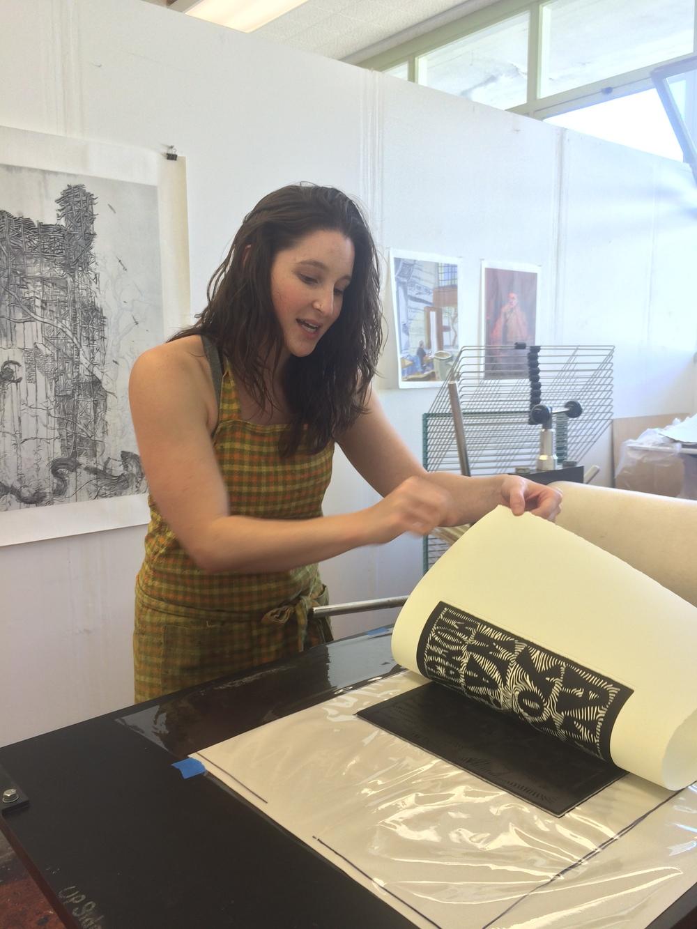 Naomi Branz prints a linoleum block on the etching press.
