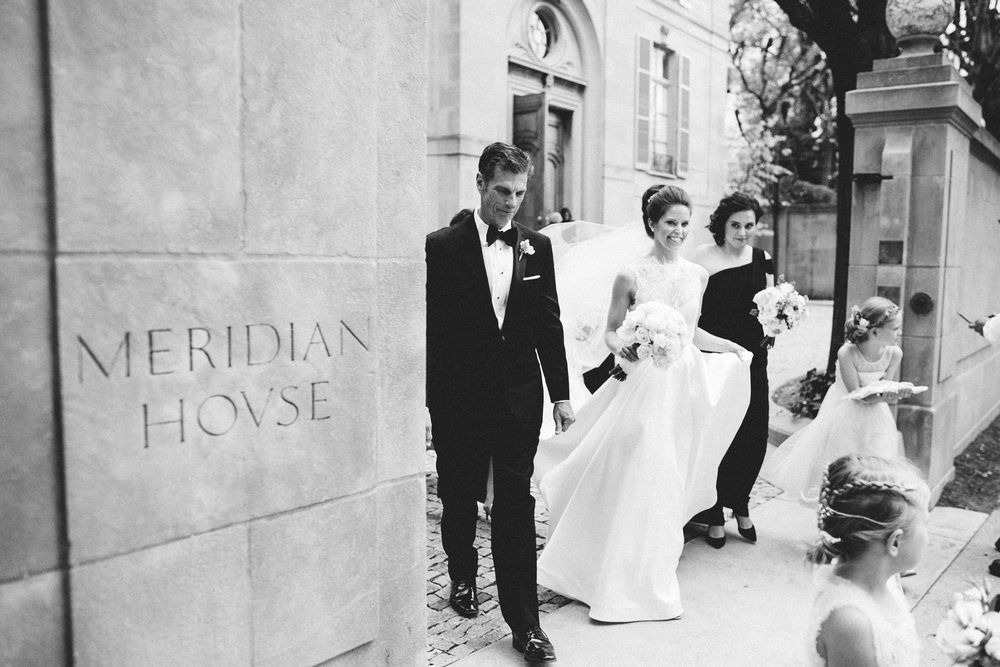 Black and white shot of bride and her family and bridal party walking to the ceremony at Meridian House in DC - Maria Vicencio Photography Weddings