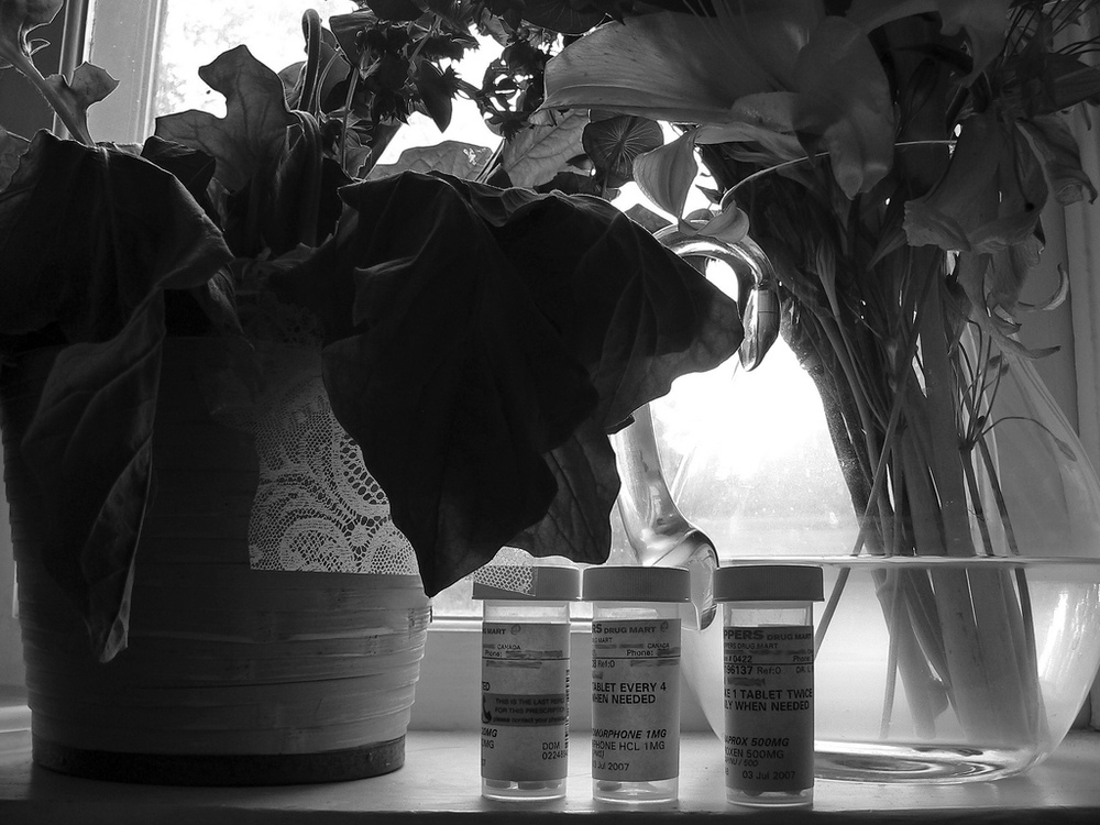 flowers and pill bottles on a bedside table