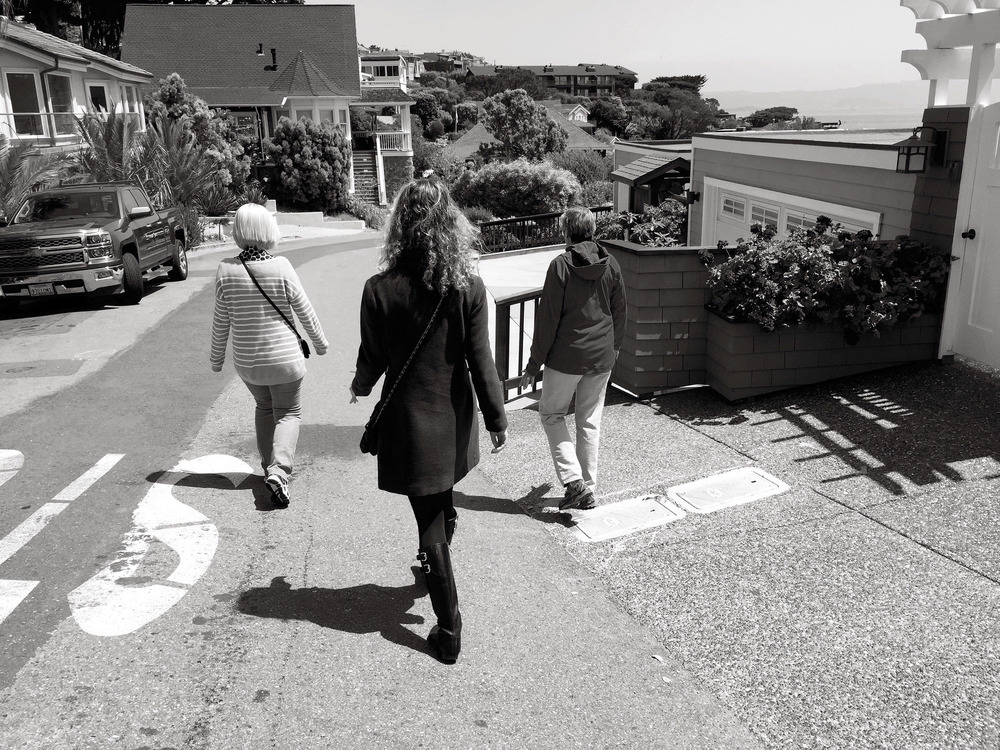 three women walking down a road together