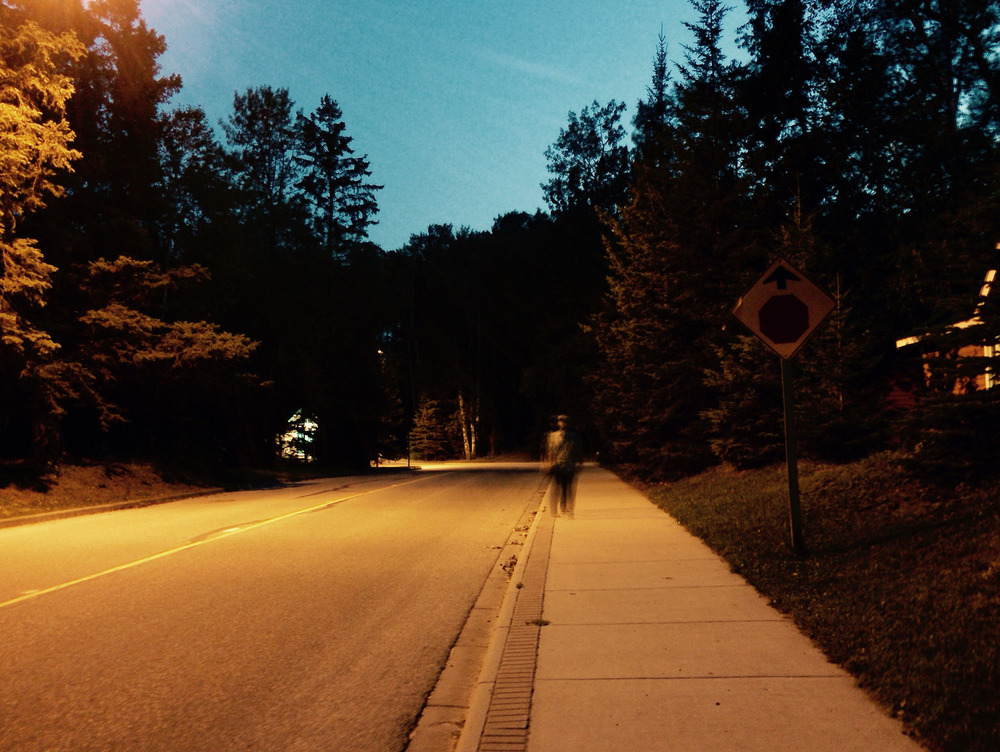 Aidan standing under a halogen streetlight acting blurry.