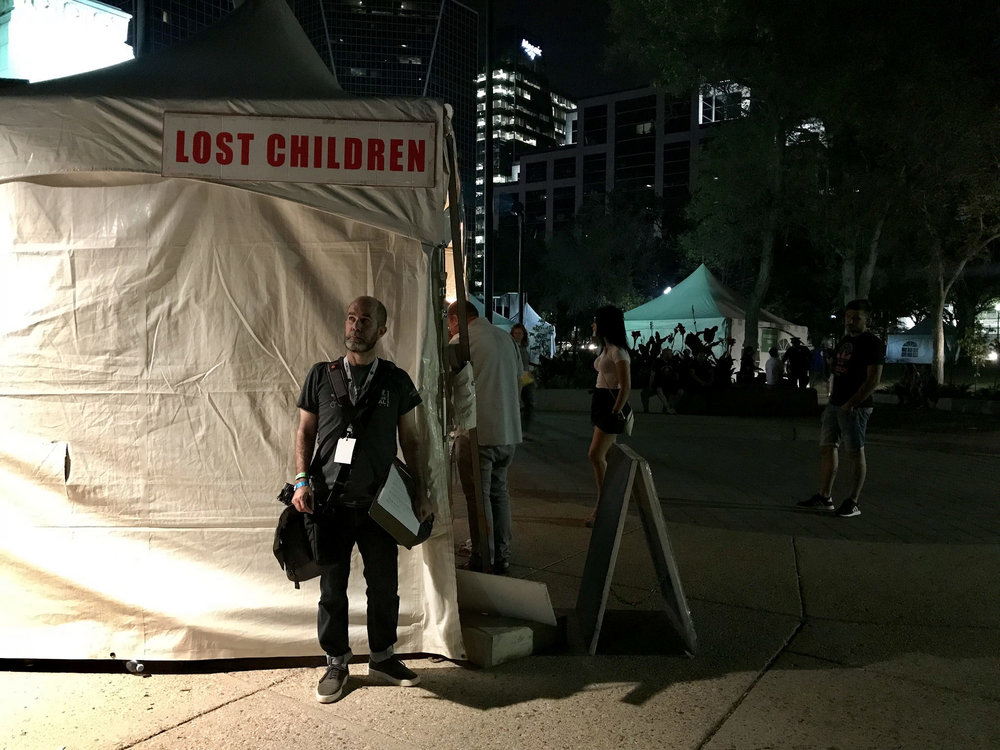 a man standing beneath a Lost Children sign at night at a festival