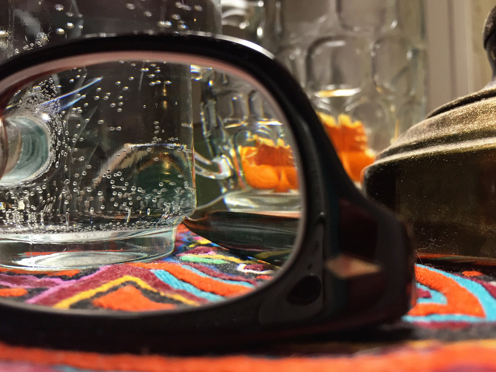 a close-up through a glasses lens to a glass of water on the other side on a bedside table