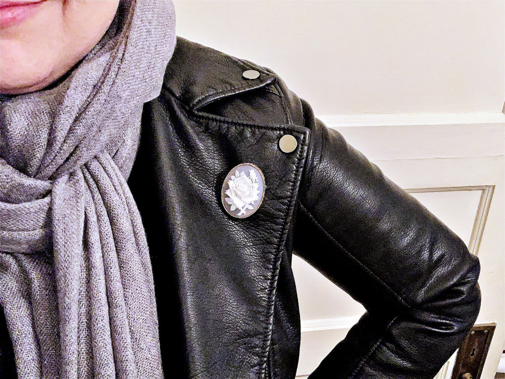 Elan with a secondhand fake cameo brooch on their leather jacket