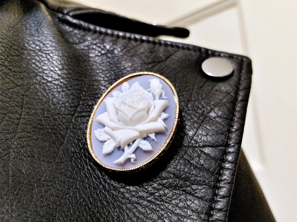 closeup of a secondhand fake cameo brooch on Elan's leather jacket