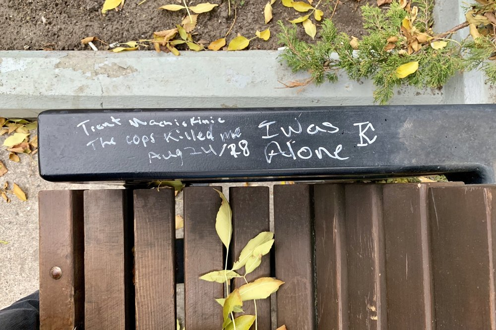 "aerial close-up of the arm on a park bench in Regina's Victoria Park with graffiti that reads ""Trent Machiskinic / The cops killed me / Aug 24/18 / I was Alone"""