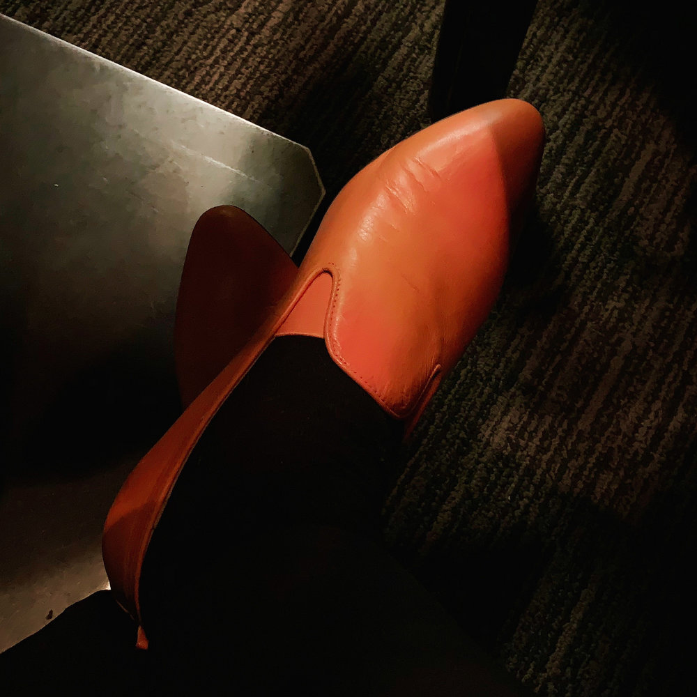 one orange leather ESH by Estée Isman slip-on shoe as seen under a table