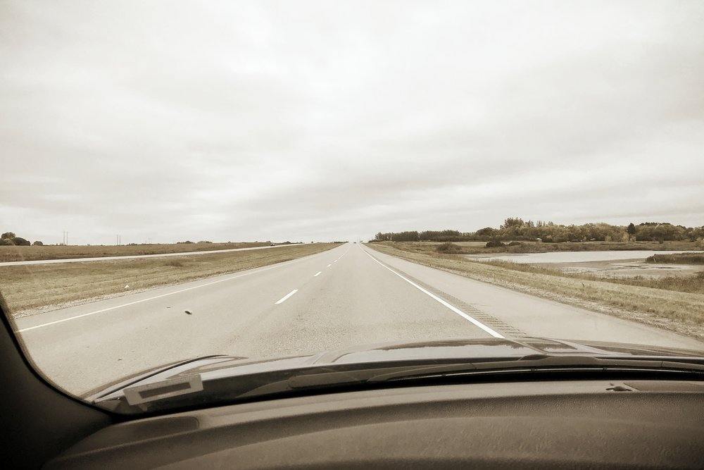 view across the dashboard through a windshield of a highway on a grey day