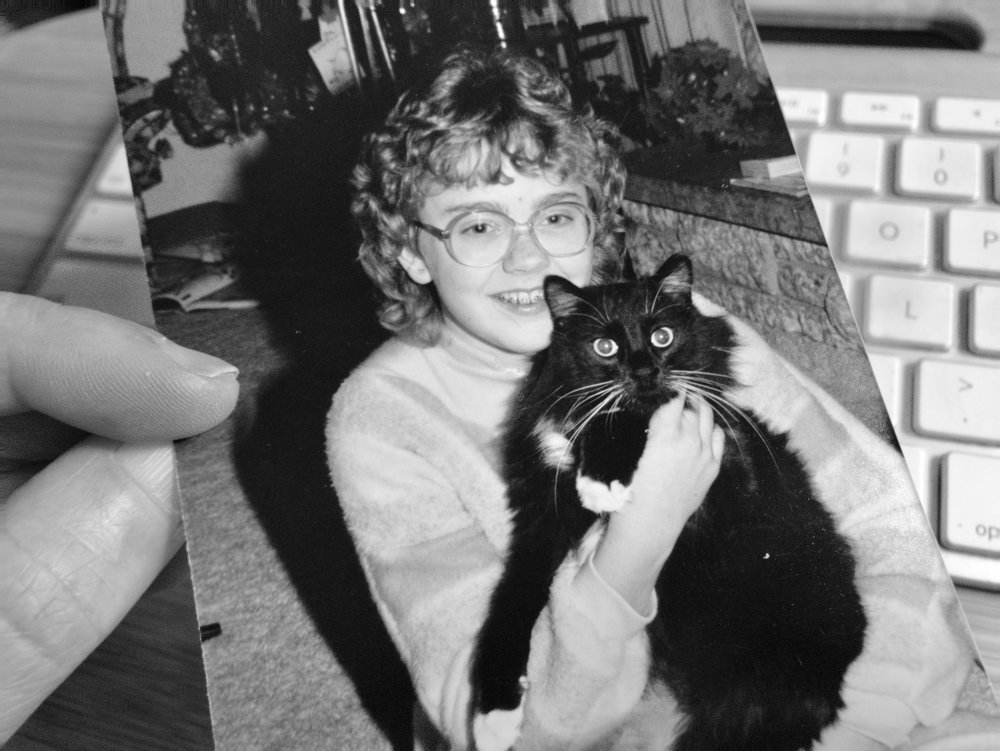 a black and white photo of a paper photograph of Elan as a kid with a fluffy tuxedo cat