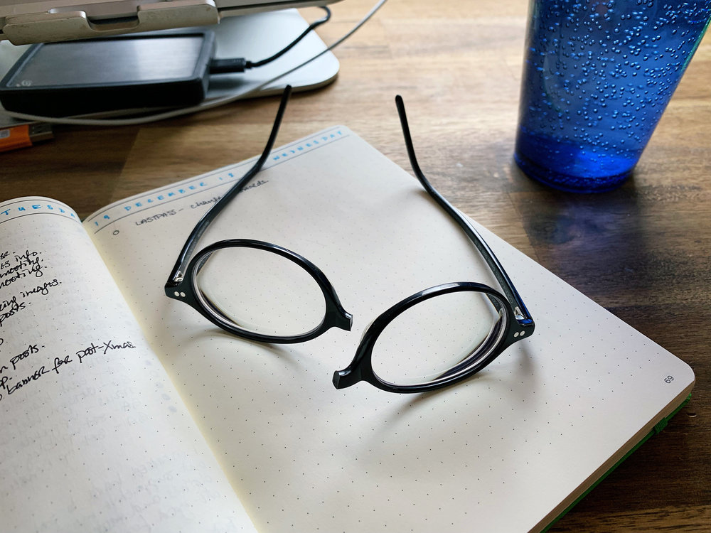 My favourite small oval glasses, broken in half, sitting in pieces on my bullet journal on my desk.