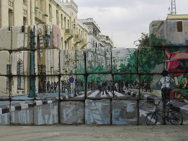Graffiti on a cinderblock wall blocking an entrance to Tahrir Square