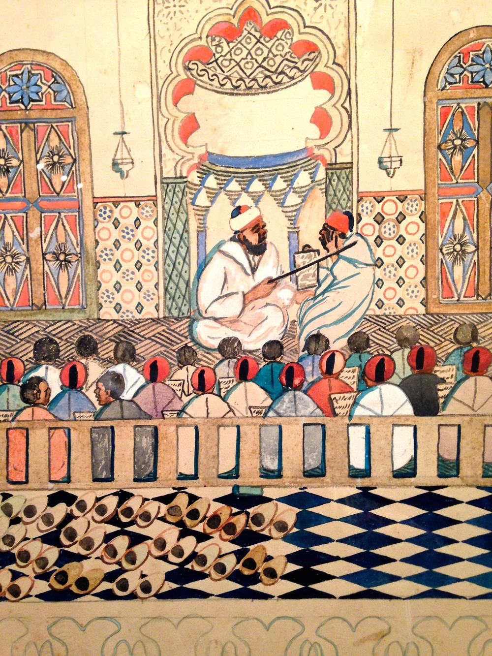 A detail from a work by the early modern  Moroccan painter Ben Ali Rbati (held at the Musée de la Fondation Slaoui in Casablanca), one of the earliest artists to use perspective and to depict more casual and domestic scenes. This is of a Coranic school.