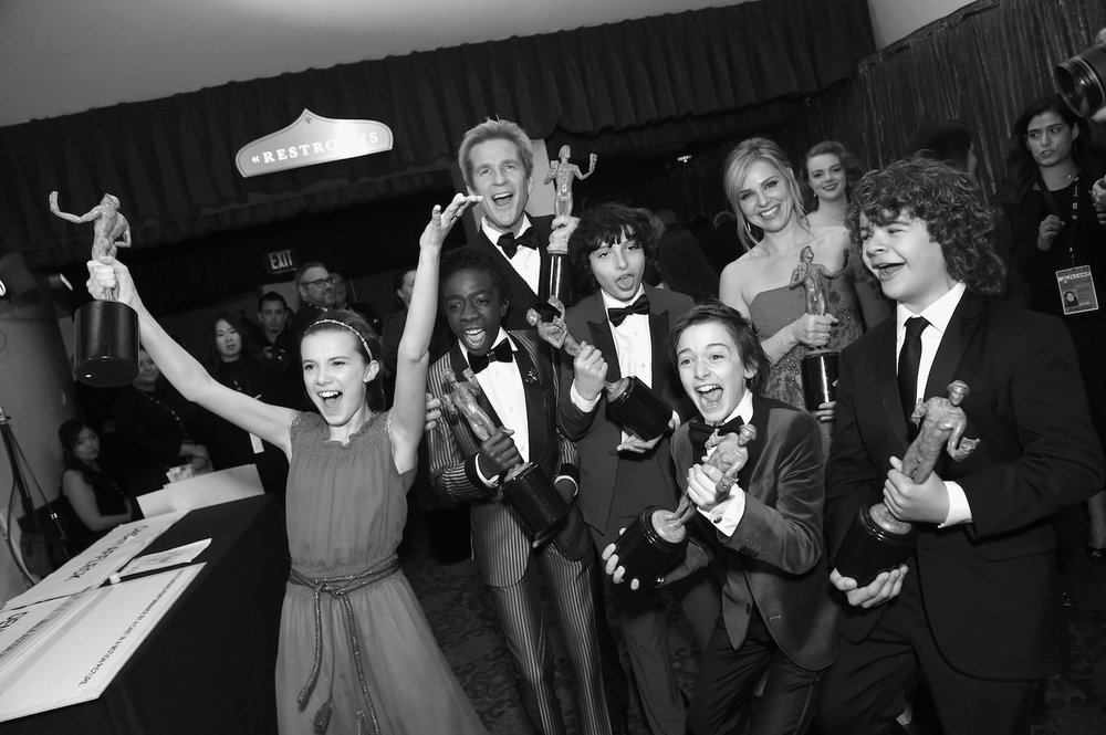 LOS ANGELES, CA - JANUARY 29:  (EDITOR'S NOTE: Image was shot in black and white.) (L-R) Actors Millie Bobby Brown, Caleb McLaughlin, Matthew Modine, Finn Wolfhard, Noah Schnapp, Cara Buono and Gaten Matarazzo, winners of the Outstanding Ensemble in a Drama Series award for 'Stranger Things,' pose during The 23rd Annual Screen Actors Guild Awards at The Shrine Auditorium on January 29, 2017 in Los Angeles, California. 26592_016  (Photo by Emma McIntyre/Getty Images for TNT) *** Local Caption *** Millie Bobby Brown;Matthew Modine;Caleb McLaughlin;Noah Schnapp;Finn Wolfhard;Gaten Matarazzo;Cara Buono