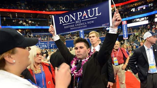A security agent calls for more security as delegate from Virginia Braedon Wilkerson displays a Ron Paul sign after the vote on Maine at the Tampa Bay Times Forum in Tampa, Florida, on August 28, 2012 during the Republican National Convention. Credit: AFP/Getty Images