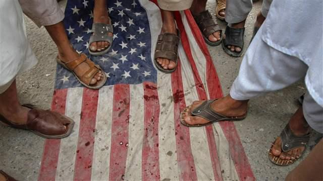 Men step on a U.S flag during an anti-American rally organized by Shabab-e-Milli, the youth wing of the Jamaat-e-Islami party, in Peshawar, Pakistan, April 13, 2012. Credit: Reuters/Fayaz Aziz