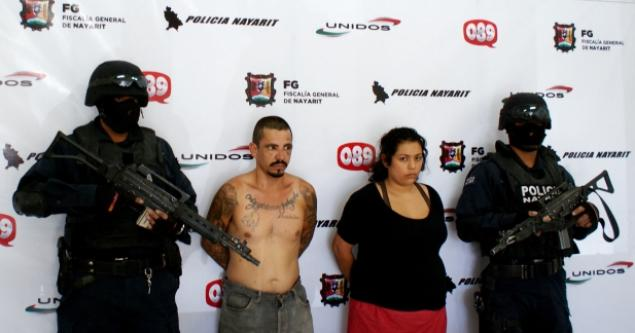 Police guard accused child rapist Eleodoro Carlos Rodriguez Sanchez and/or Carlos Roberto Tapia Sanchez, aka, 'El Cholo' (2nd from left), and his ex-girlfriend, Nancy Saralee Solorio Perez, after their arrest in the city of Tepic, Mexico.