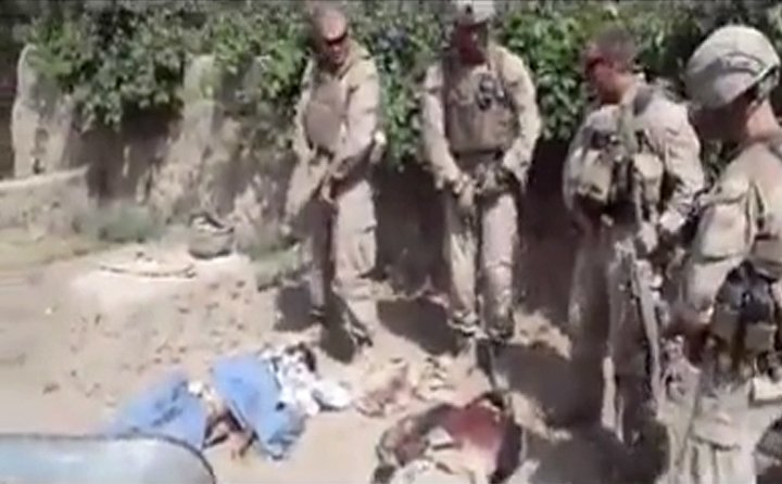 """Photo by: Anonymous  ** FILE ** This image made on Jan. 12, 2012, from an undated video posted on the Internet by a YouTube user self-identified as """"semperfiLoneVoice"""" shows men in U.S. Marine combat gear standing in a semicircle over three bodies. U.S. Defense Secretary Leon E. Panetta branded as """"utterly despicable"""" the video purporting to show four U.S. Marines urinating on the corpses of Taliban fighters. (Associated Press)"""