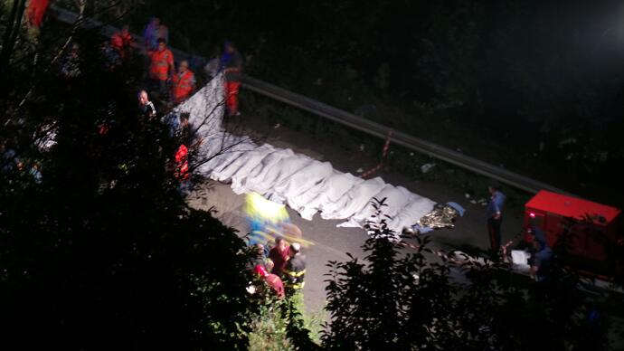 Rescuers line up the bodies of victims of a bus crash on July 28, 2013 on the road between Monteforte Irpino and Baiano, southern Italy (AFP Photo / Stringer / Agenzia Controluce)